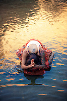Woman in the water with her hands in namaste.