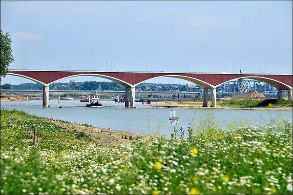 Nederland, Nijmegen, 25-6-2015 De nevengeul aan de overkant van de Waal bij Lent nadert zijn voltooiing. Grootste onderdeel van de vele werken van Rijkswaterstaat om bij hoogwater een betere waterafvoer in de rivier te hebben. Bij de nieuwe recreatiekade. Het is een omvangrijk project waarbij onder meer de pijlers van het spoorviaduct een bredere basis kregen omdat die straks in de loop van het water staan. Ook de n325 die vanaf de Waalbrug naar Arnhem loopt ist over 400 meter opnieuw worden aangelegd omdat het talud vervangen wordt door een nieuwe brug met drie gracieuze pijlers. De weg werd via een bypass omgeleid. Het dorp veurlent komt op een kunstmatig eiland te liggen met twee bruggen als ontsluiting. Een voetgangersbrug en een andere, de Promenadebrug, voor normaal verkeer. Inmiddels begint de nieuwe kade aan de noordkant van deze geul vorm te krijgen. Ruimte voor de rivier, water, waal. In de nieuwe dijk wordt een drempel gebouwd die stapsgewijs water doorlaat en bij hoogwater overloopt. The Netherlands, Nijmegen Measures taken by Nijmegen to give the river Waal, Rhine, more space to flow during highwater and to prevent the risk of flooding. Room for the river. Reducing the level, waterlevel. Large project to create a new paralel gully, an extra flow of water, so the river can drain more water during highwater. Due to climate change and expected rise, increase of the sealevel, the Dutch continue to protect their land from the water. Foto: Flip Franssen/Hollandse Hoogte