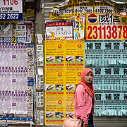 Lady walking past wall of advertising posters in Hong Kong