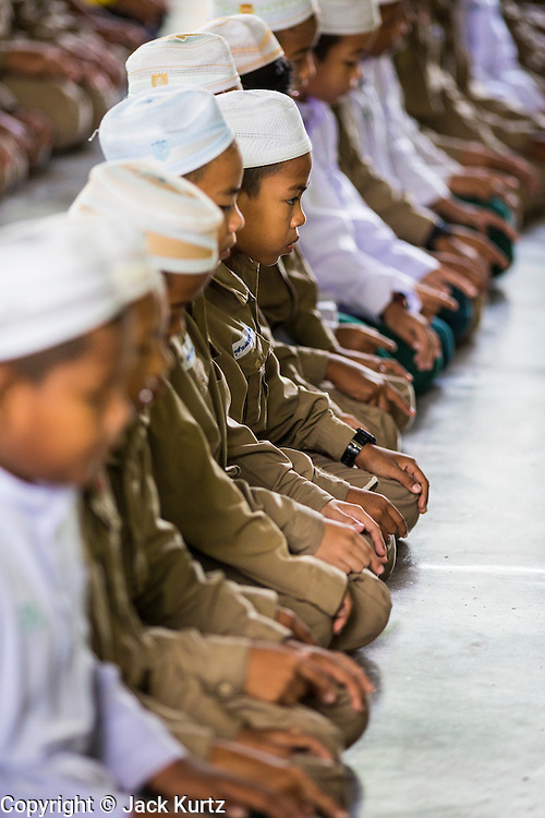 10 JULY 2013 - PATTANI, PATTANI, THAILAND: Students at morning prayers in a private Muslim school in Pattani, Thailand. Many Muslim parents prefer to send their children to Muslim private schools because they are safer (public schools have been attacked by Muslim insurgents), the Muslim schools teach an Islam centric curriculum and teach what many in Pattani consider a more accurate version of Pattani history.   PHOTO BY JACK KURTZ