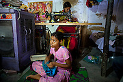 Arti, 15, Poonam's eldest sister, (front) is taking stitching lessons in Oriya Basti, one of the water-affected colonies in Bhopal, Madhya Pradesh, India, near the abandoned Union Carbide (now DOW Chemical) industrial complex.