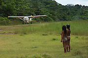 Huaorani Indians, Awame Gomoke & Beñemo Bopoga waiting for light aircraft coming into the Huaorani Indian community.<br /> Bameno Community. Yasuni National Park.<br /> Amazon rainforest, ECUADOR.  South America<br /> This Indian tribe were basically uncontacted until 1956 when missionaries from the Summer Institute of Linguistics made contact with them. However there are still some groups from the tribe that remain uncontacted.  They are known as the Tagaeri & Taromenane. Traditionally these Indians were very hostile and killed many people who tried to enter into their territory. Their territory is in the Yasuni National Park which is now also being exploited for oil.
