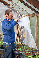 Preparing a greenhouse for winter - putting up bubble wrap insulation