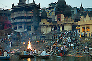 Tourists watch body bathed in River Ganges and traditional Hindu cremation on funeral pyre at Manikarnika Ghat in Holy City of Varanasi, Benares, India RESERVED USE - NOT FOR DOWNLOAD -  FOR USE CONTACT TIM GRAHAM