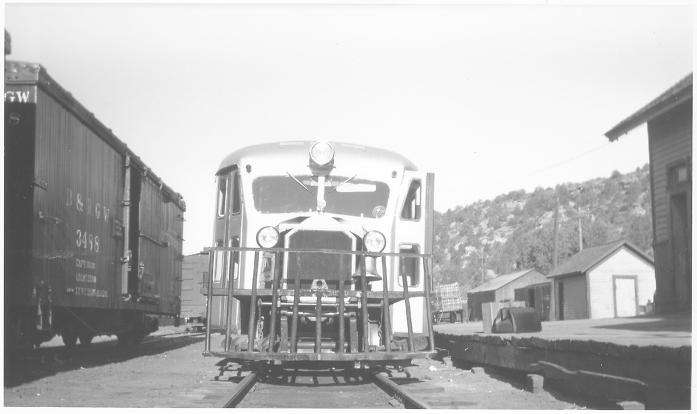 RGS Goose #5 (?) at Dolores depoit platform with boxcar #3488 to the left.  Station outhouse is to the right in the background.<br /> RGS  Dolores, CO  Taken by Peyton, Ernie S. - 6/1946