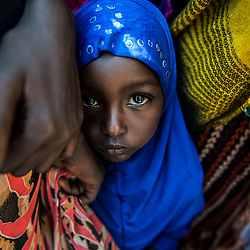 A Borana girl hides behind her mother's abaya in  Isiolo, Kenya during a funeral for a slain ranger. Northern Kenya has a history riddled with violence, primarily between livestock herders of warring tribes. Competition for pasture and water, especially during times of drought, force different tribes to migrate to the same area and often leads to conflict. Cattle raiding has a long history in this area too and AK-47s imported from Somalia are easily acquired on the black market in towns like Isiolo. These years of fighting have taken their toll on the communities, wildlife and habitats of Northern Kenya, which is why the Northern Rangelands Trust is working with these communities to improve security and build relationships between the communities.
