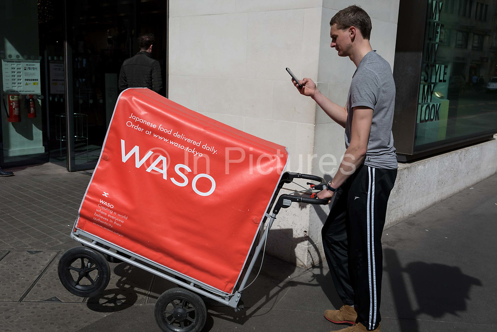 A delivery man wheels his Japanese food cart through the Square Mile, the capitals financial district, on 3rd March 2017, in the City of London, England.