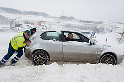 © Licensed to London News Pictures. 2/03/2018. Brynmawr, Blaenau Gwent,, South Wales, UK. 'Good Samaritan' men from a gritting truck help a stranded motorist who has got stuck near the Heads of Valley road near Brynmawr. People battlle against the blizzard, snowdrifts and horrendous weather conditions as Storm Emma continues without mercy at Brynmawr in South Wales (the highest town in Wales.)  Photo credit: Graham M. Lawrence/LNP