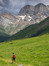 Woman hiking in the High Pyrenees descending Oulettes d'Ossoue towards Gavarnie, France