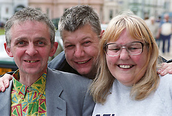 Group of people with learning disabilities standing together smiling,