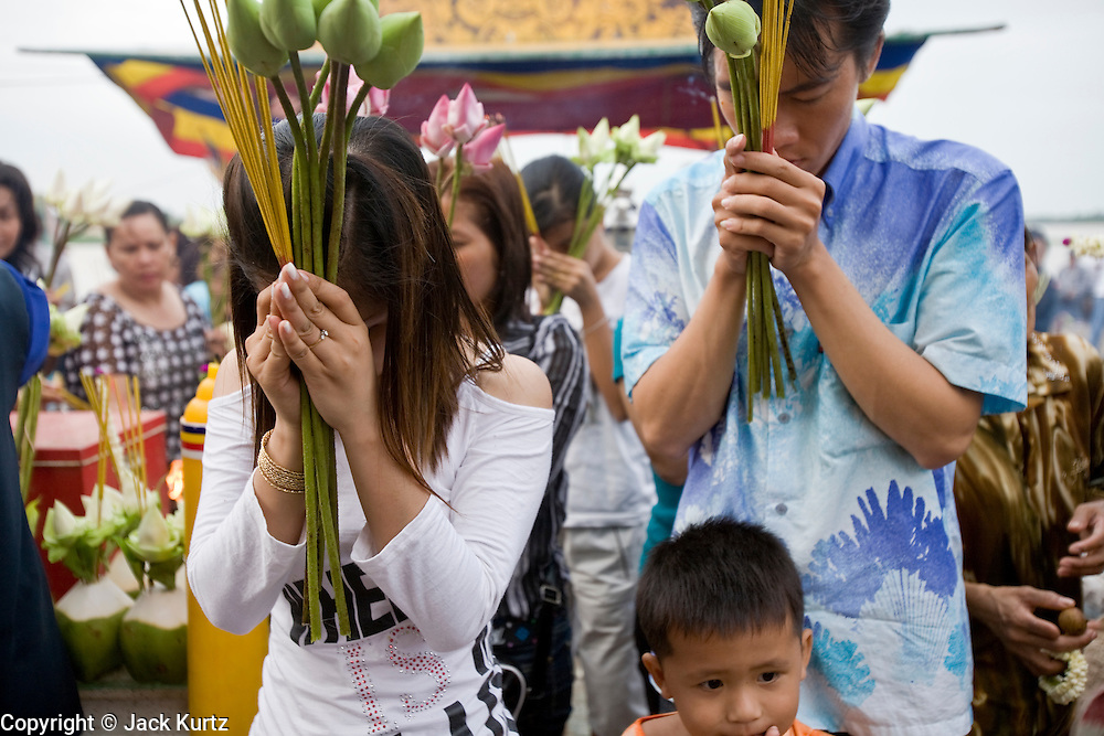 """03 JULY 2006 - PHNOM PENH, CAMBODIA: People crowd into a small pagoda in front of the Royal Palace in Phnom Penh, Cambodia to pray. The pagoda serves as the """"spirit house"""" of the palace. The Cambodians (and Thais) build small spirit houses, which have great religious significance, in front of the homes and usually businesses. They pray at the spirit homes and frequently leave small offerings of fruit and small change in them. The spirit house for the Palace has become a public shrine and there are usually people there praying, leaving donations and lighting incense.      PHOTO BY JACK KURTZ"""