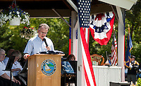 Selectman Kevin Hayes reads a message from Senator Kelly Ayotte and afterwards presents the American Flag to Gilford Police Chief Kevin Keenan during the Gilford Bicentennial events at the Village Field Saturday morning.   (Karen Bobotas/for the Laconia Daily Sun)