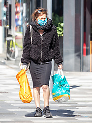© Licensed to London News Pictures. 05/05/2020. London, UK. A women in a mask and gloves goes shopping in Putney High Street, South West London. Wearing masks while out shopping or travelling on public transport could be the new normal as Ministers and scientists decide if it would help after official figures reveal that the UK now has Europe's highest Covid-19 death toll. This Sunday, Prime Minister Boris Johnson prepares to tell the nation of his plans on easing lockdown and how the new normal will work as the coronavirus pandemic crisis continues. Photo credit: Alex Lentati/LNP