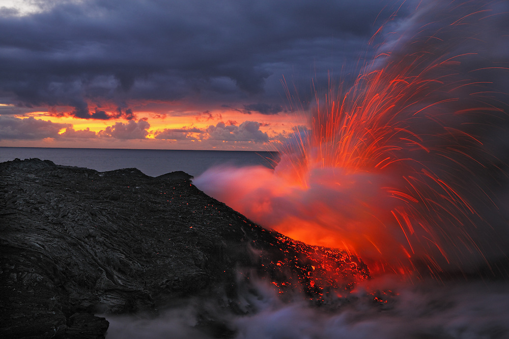 A fiery littoral explosion, generated by lava induced superheated steam, rocks the Kalapana coast at daybreak.