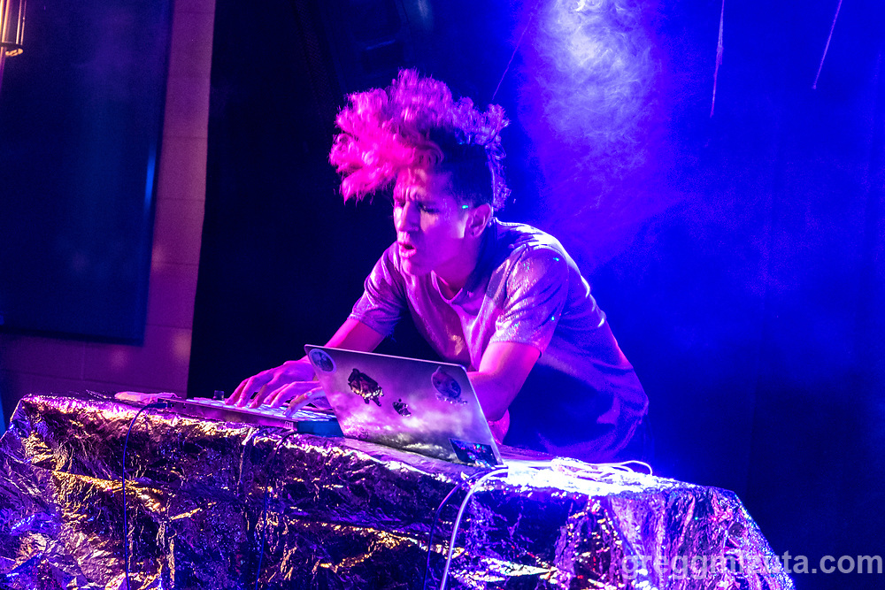 """Rocky Wing. HE/LIUM SHE/LIUM performs at the Boise Hive, Boise, Idaho on August 21, 2021.<br /> <br /> HE/LIUM SHE/LIUM is an 80's inspired, synth pop, electronic, dance duo.<br /> <br /> They started when partners Ari Wing and Rocky Wing found themselves in a small apartment in Boise, ID. With no connections, working full-time, going to school, lack of practice space, and the noise limits of apartment living, they decided to go fully electronic. (No real instruments are harmed in the making of their music.)<br /> <br /> Ari plays keytar and sings. Rocky plays all the other sounds on a midi controller. What makes them unique is that, although they play loops, they actually create those loops in real time while they are playing. So that means that if they make a mistake (or reinterpretation!) it repeats for the whole song. It makes for exciting, spontaneous live shows.<br /> <br /> Their sound is infectious and will get you on your feet. Don't be surprised if you are singing along to a song you just heard! Yet at the same time their connection to each other, their music, and the audience is authentic and genuine. Their lyrics balance beautifully between the bleak reality of past rejection and the positive vibes that is their life together now. Even their sound guy at one of their shows confessed afterwards """"I usually like dark metal. I don't want to like you guys. But I can't help it -- I love HE/LIUM SHE/LIUM!"""""""