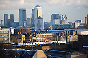 The view of the Isle of Dogs 20th November 2015. Canary Wharf on the Isle of Dogs is one of Londons financial districts and it is surrounded by housing and council estates in the boroughs of Tower Hamlets. In the foreground passes a train coming from London Liverpool Street Station.