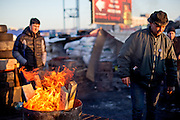 """Activists Bosch (2nd left) after lightning a fire for heating at the barrikades blockading a building supplies store named """"Epicenter"""" in the city of Lviv, Ukraine. Two people passing by."""