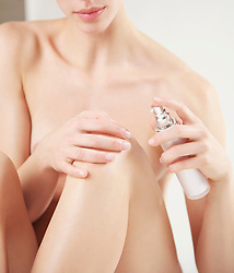 Close up of a nude woman applying cosmetic cream on her knee