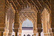 Carved stucco arabesques and Arabic scripture adorn the arches and columns of the Court of the Lions in the Casa Real complex, La Alhambra, Granada, Andalusia, Spain.