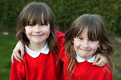 Young twin sisters with their arms around each other,