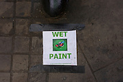 Warning of Wet Paint, taped to the pavement in a central London sidestreet.