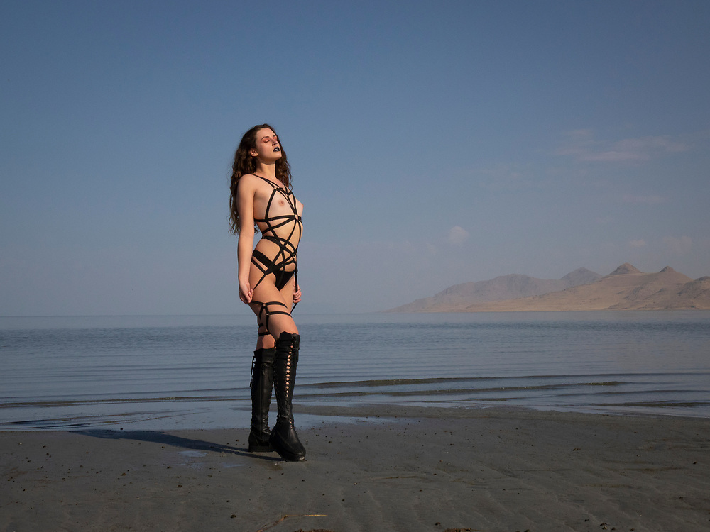 Nude woman in boots and straps outfit posing next to the Great Salt Lake, Utah