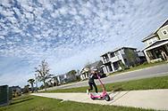A child rides a scooter in the Laureate Park neighborhood of the Lake Nona development of Orlando, Fla., Saturday, Jan. 30, 2016. (Phelan M. Ebenhack via AP)