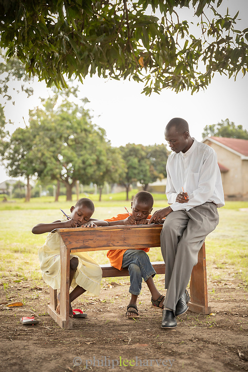 View of children sitting at desk and writing while teacher is explaining, The Musoto Christian School, Uganda