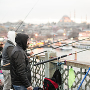 Fishermen line the edge of Galata Bridge with their lines over the side into the Golden Horn. Spanning the Golden Horn and linking Eminonu with Karakoy, the Galata Bridge is a dual-level bridge that handles road, tram, and pedestrian traffic on the top level with restaurants and bars on the level below. In the distance is Suleymaniye Mosque.