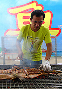 NANNING, CHINA - SEPTEMBER 05: (CHINA OUT) <br /><br /><br />A man sells grilled crocodile meat during a food festival on September 5, 2013 in Nanning, Guangxi Province of China. <br />©Exclusivepix