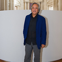 """VENICE, ITALY - MAY 31:  Artist Anish Kapoor stands in front of his installation """"Ascension"""" during the press opening at Basilica di San Giorgio on May 31, 2011 in Venice, Italy. """"Ascension"""" is an installation that cosnist of a column of white smoke rising from a circular base placed at the intersection between the transet and the nave of Basilica of San Giorgio Maggiore"""