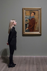"""© Licensed to London News Pictures. 21/11/2017. London, UK.  A staff member views """"Self-Portrait"""", 1919.  Preview of """"Modigliani"""", the most comprehensive exhibition of works by Amedeo Modigliani ever held in the UK.  On display are iconic portraits, sculptures and 12 nudes, the largest group ever shown in the UK.  The show runs 23 November to 2 April 2018.  Photo credit: Stephen Chung/LNP"""