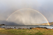 Rainbow over Runde bridge, Norway with a rain squall inn the background | Regnbogen over rundebroa, med en regnbyge i bakgrunnen.
