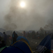 Syrian refugees are seen standing outside their tents, after a night of heavy rain fall, at the Greek-Macedonian border station of Idomeni, Greece. Around 13,000 migrants and refugees, mostly from the Middle East and African nations, are believe to be stranded here awaiting a chance to proceed their journey towards Germany and other northern European countries.