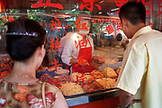Chopped cooked meats and pickled vegetables are served to customers from a hatch at a street market painted in Chinese characters on Renmin Lu in Shanghai, China. This is a common sight on many streets.