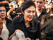 11 NOVEMBER 2016 - BANGKOK, THAILAND: YINGLUCK SHINAWATRA greets supporters at a rice distribution sale in the Bangkok suburbs. Yingluck Shinawatra, the former Thai Prime Minister deposed in a coup in 2014, has started selling rice directly to Thai consumers. She buys the rice from farmers at market prices and then sells it to urban consumers at the price she paid. She said she's doing it to help out farmers, who are trying to deal with depressed prices. Yingluck is facing prosecution on corruption related charges going back to a rice price support scheme her government used to try to help farmers in 2011 and 2012. Even after the coup, she is still personally popular and hundreds of people showed up to see her at the rice distribution point at a mall in Samut Prakan province, in suburban Bangkok.   PHOTO BY JACK KURTZ