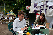 Balcombe, West Sussex. Site of Cuadrilla drilling. Demonstration against fracking 18.08.2013. Journalists writing in front of the site entrance.