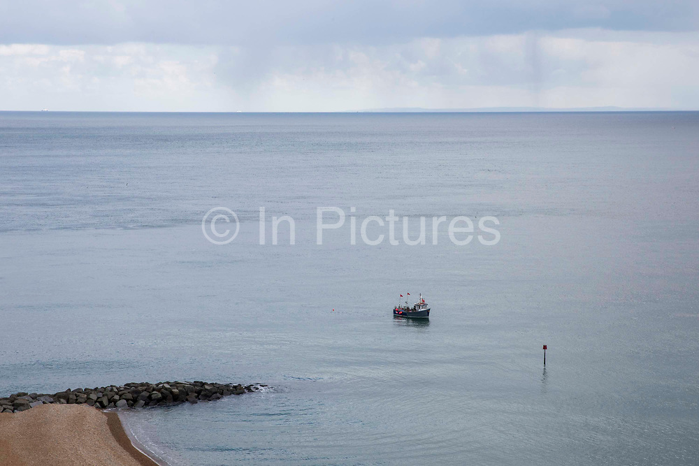 A British fishing boat laying down pots to catch crab and lobsters off the coast of Folkestone in the English Channel. United Kingdom. Ferries and France can be seen on the horizon.
