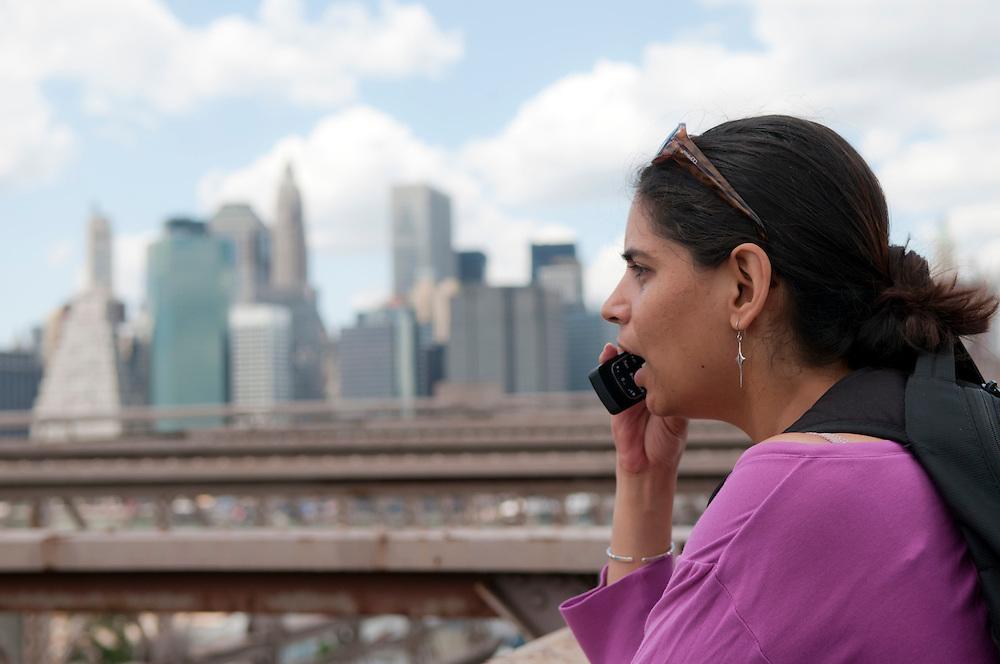 Eine junge Frau steht auf der Brooklyn Bridge in New York und führt ein Telefonat mit einem Mobiltelefon   |  young woman talsk on a mobile phone in New York    |