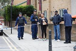 © Licensed to London News Pictures. 15/10/2015. London, UK. Police speak to local residents at the scene of a shooting in Haggerston, Hackney on the corner of Lovelace Street and Haggerston Road. Photo credit : Vickie Flores/LNP