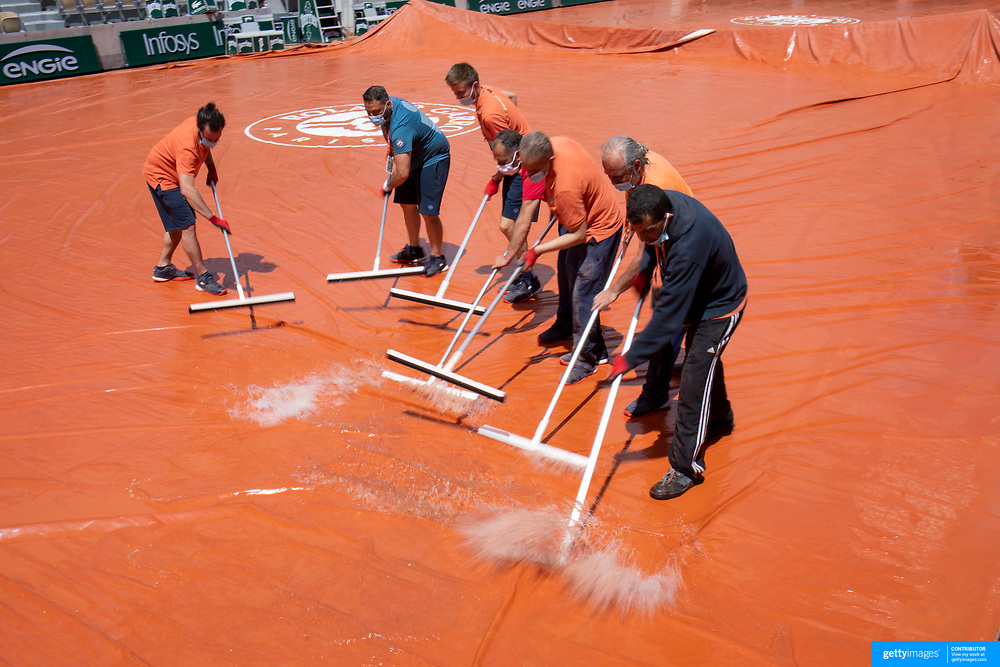 PARIS, FRANCE May 24.  Ground staff remove water from the covers of Court Suzanne Lenglen on a rainy day in Paris as they prepare the courts during the first day of the qualifying tournament at the 2021 French Open Tennis Tournament at Roland Garros on May 24th 2021 in Paris, France. (Photo by Tim Clayton/Corbis via Getty Images)
