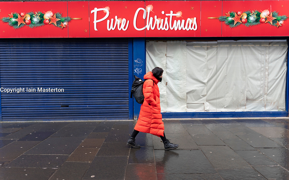 Glasgow, Scotland, UK.1 December 2020. Coronavirus health warnings, shop display and graffiti in Glasgow city centre. Pictured; Woman in red walks past a closed and shuttered speciality Christmas shop.  Iain Masterton/Alamy Live News