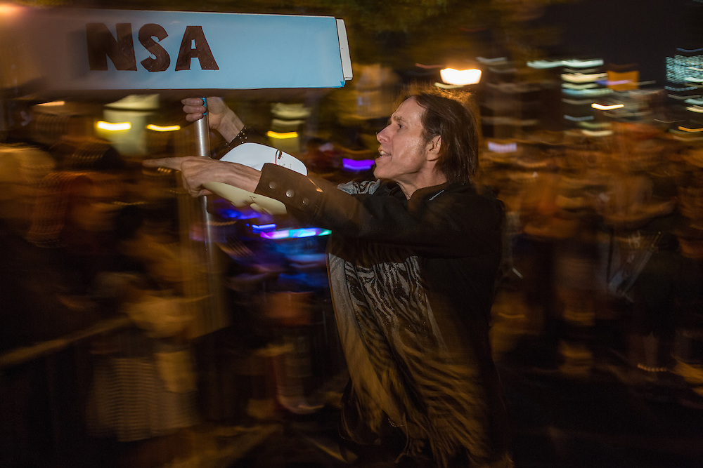 """New York, NY, October 31, 2013. A man aims a prop spy camera labeled """"NSA"""" at the crowd in the Greenwich Village Halloween Parade."""