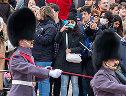 © Licensed to London News Pictures. 11/03/2020. London, UK. A couple in medical masks watch the Changing of the Guards at Buckingham Palace as Health Minister, Nadine Dorries goes in to self-isolation after catching Covid19. Yesterday British Airways cancelled all flights to and from Italy as fears over the Coronavirus disease continues. Photo credit: Alex Lentati/LNP