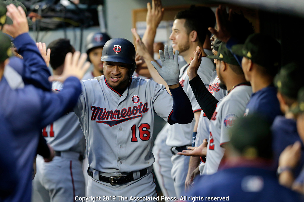 Minnesota Twins' Jonathan Schoop celebrates a three-run home run in the dugout against the Seattle Mariners during a baseball game, Saturday, May 18, 2019, in Seattle. (AP Photo/John Froschauer)