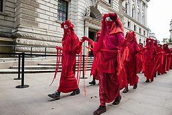 Members of the Red Rebel Brigade pass the Treasury after leaving the Back The Bill rally by fellow climate activists from Extinction Rebellion in Parliament Square on 1st September 2020 in London, United Kingdom. Extinction Rebellion activists are attending a series of September Rebellion protests around the UK to call on politicians to back the Climate and Ecological Emergency Bill (CEE Bill) which requires, among other measures, a serious plan to deal with the UK's share of emissions and to halt critical rises in global temperatures and for ordinary people to be involved in future environmental planning by means of a Citizens' Assembly.