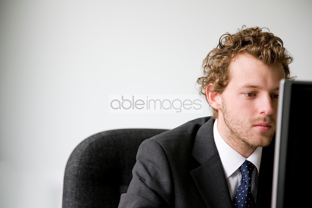 Close up of young businessman working on computer