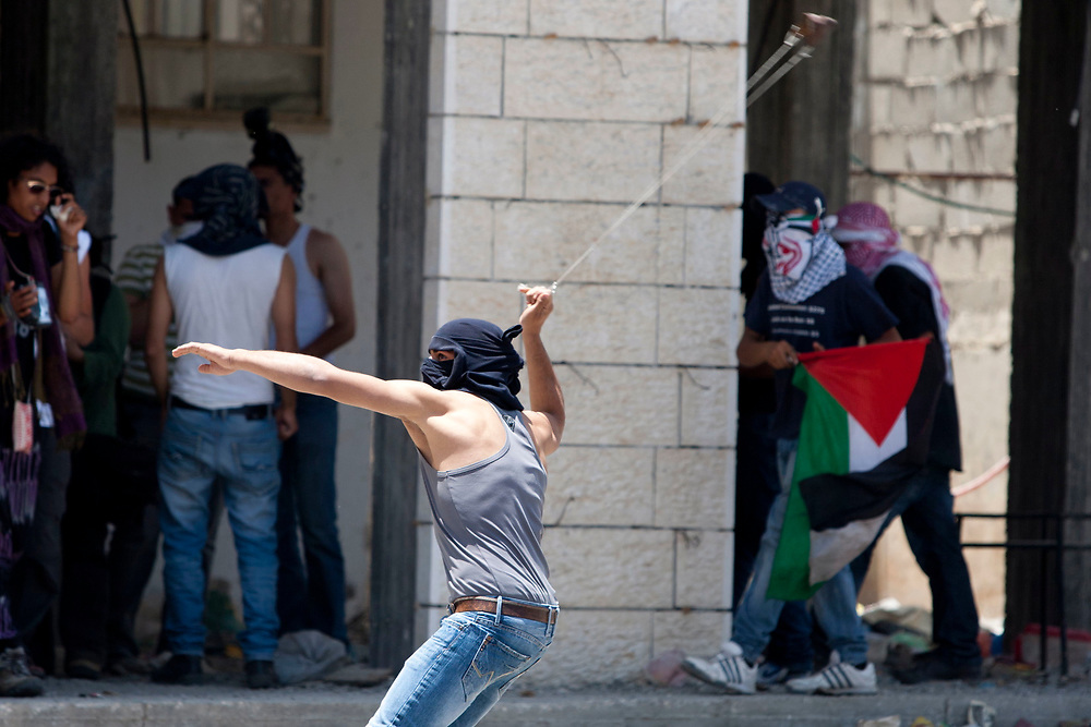 A Palestinian demonstrator hurls stones at Israeli soldiers, not seen, during clashes with Israeli troops at the Qalandiya checkpoint, between Jerusalem and the West Bank city of Ramallah, on June 5, 2011. Palestinians Mark The 44th Anniversary of the 1967 Six Day War.