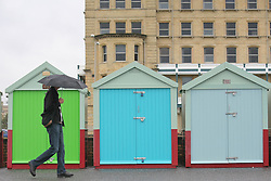 © under license to London News Pictures. 12/06/12. Heavy rainfall across the south east, a Man walks with a an unbrella on brighton seafront next to some brightly coloured beach huts. The met office has issued severe weather warnings in England and Wales. Unseasonal weather in the south east has caused flooding. Sussex has been badly hit. Brighton XAVIER ITTER/LNP