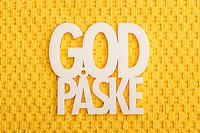 Norsk påskehilsen «God påske» med hvit tekst mot gul bakgrunn med struktur av grovt stoff.